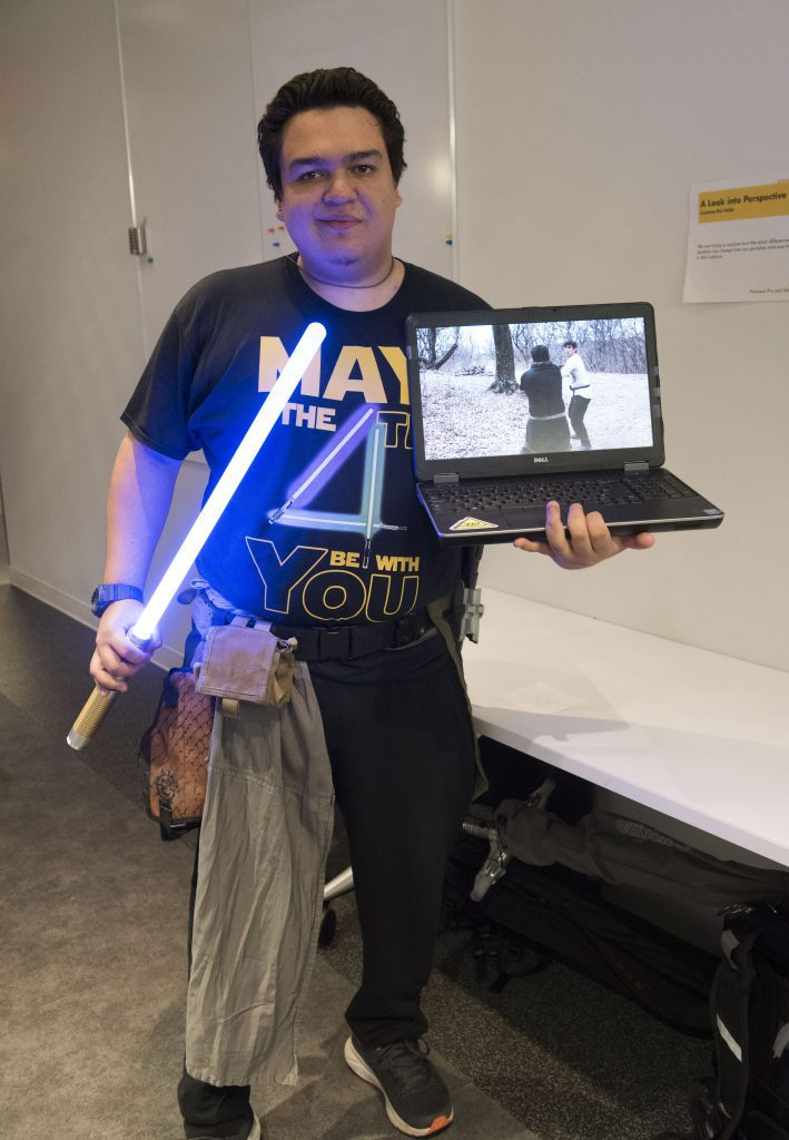 Student presenting their work on a laptop and a lightsaber at IDM showcase 2018