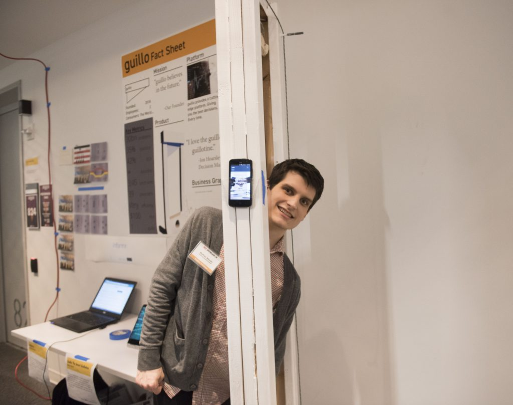 Student interacting with a student project which includes a physical installation and mobile phone at IDM showcase 2018