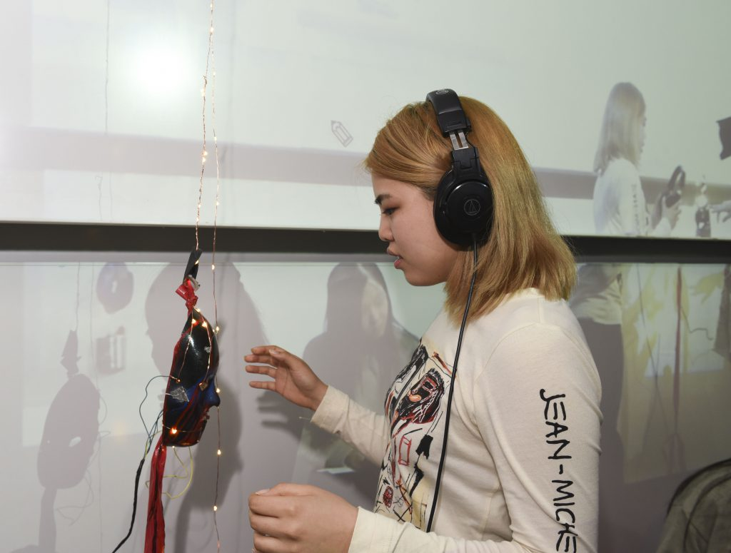 Student interacting with a physical prototype which is a mask with LED lights and wearing headphones at IDM showcase 2017