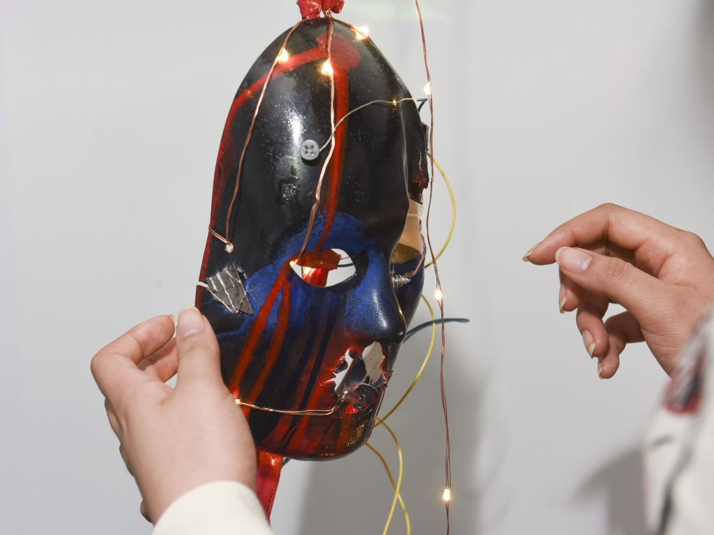 Student interacting with a physical prototype which is a mask with LED lights at IDM showcase 2017