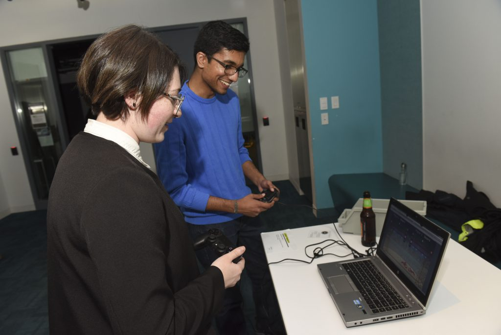 Students interacting with student project which is a controller based game on a laptop at IDM showcase 2017