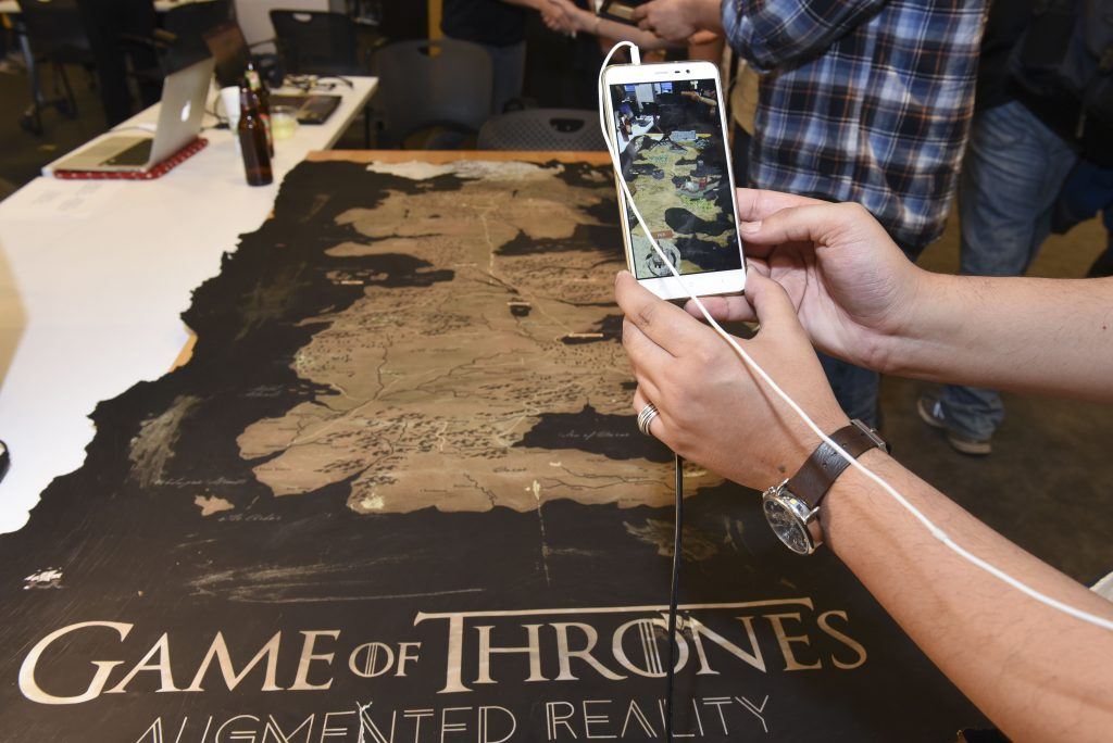 Student interacting with a mobile AR game of thrones themed project at IDM showcase 2017