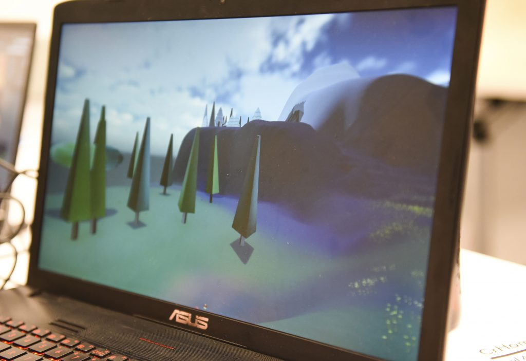 Student project on a laptop at IDM showcase 2017 showing a 3D landscape with trees, mountains and clouds in the sky