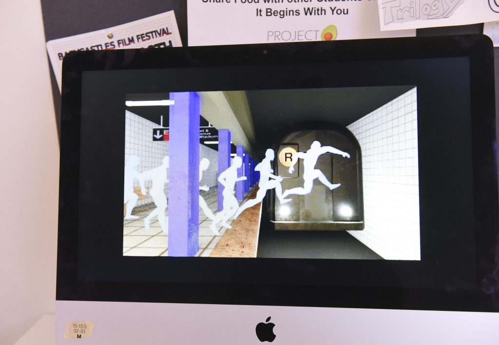 Student project on a monitor at IDM showcase 2017 showing white body shadows jumping in front of a subway train