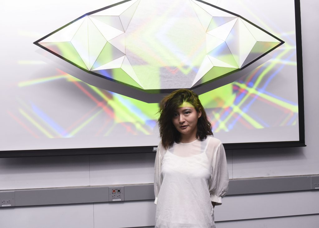 Student presenting a project which includes an eye shaped physical installation at IDM showcase 2017