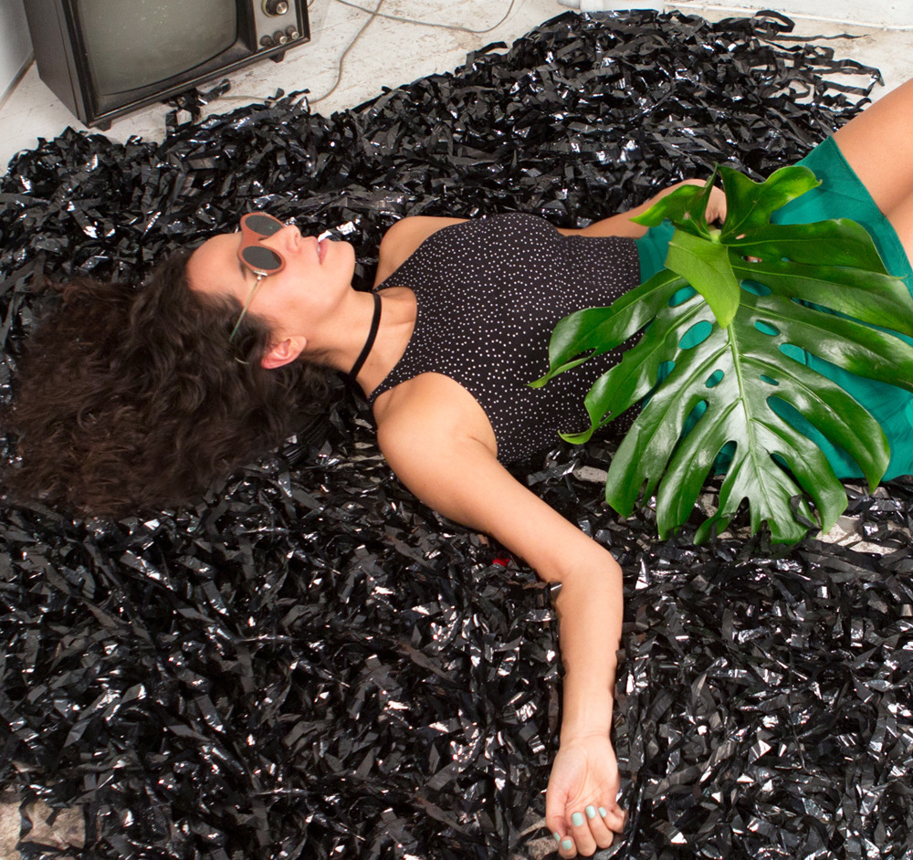 Diana Castro NYU IDM Alumni posing on what looks like a bunch of cassette tape rolls