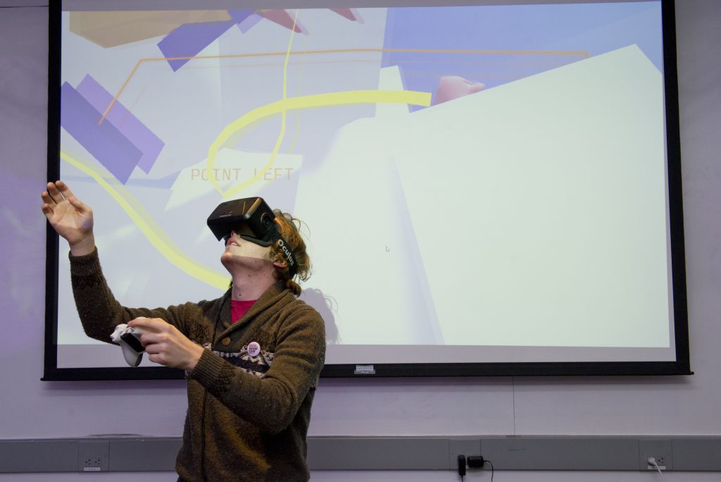 student interacting with a VR project at IDM 2016 showcase