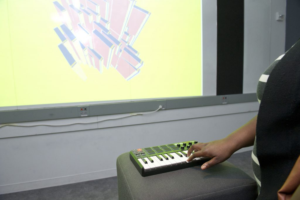 student interacting with a screen projected project through a musical keyboard at IDM 2016 showcase